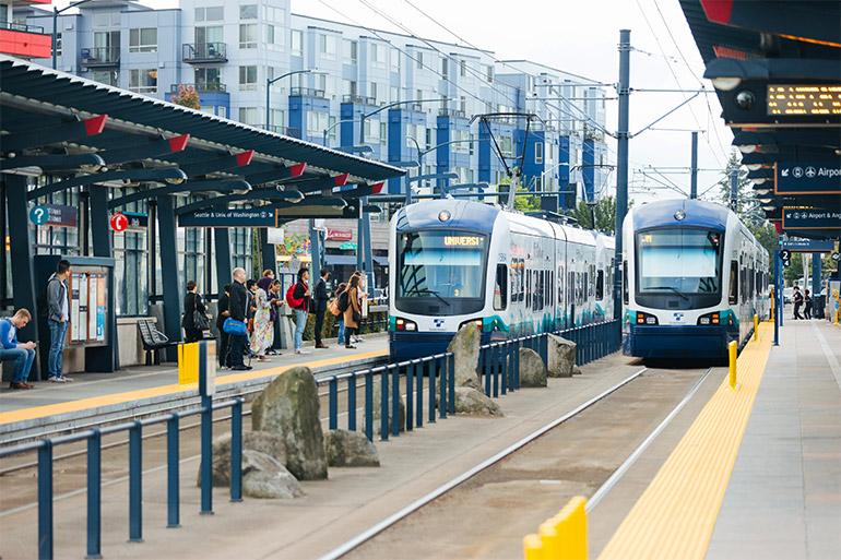 La gente espera en una estación de Link para abordar dos trenes ligeros